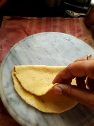 Grease the chapati and fold in half